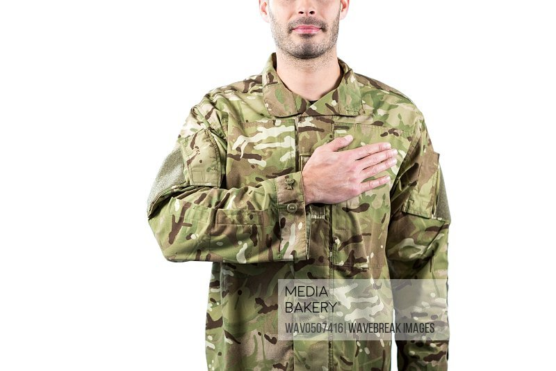 Mid section of soldier taking oath against white background
