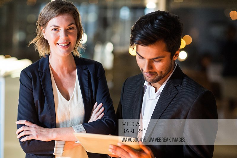 Portrait of businessman discussing with colleague over digital tablet in the office