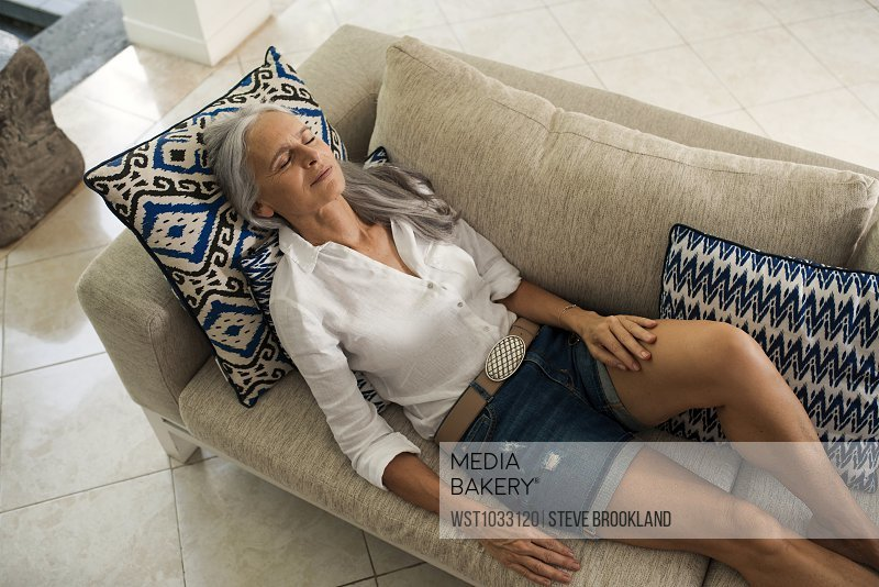 Attractive Senior Woman Relaxing On Couch