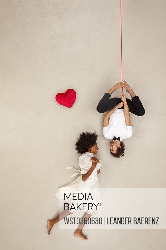 Couple falling in love man hanging upside down