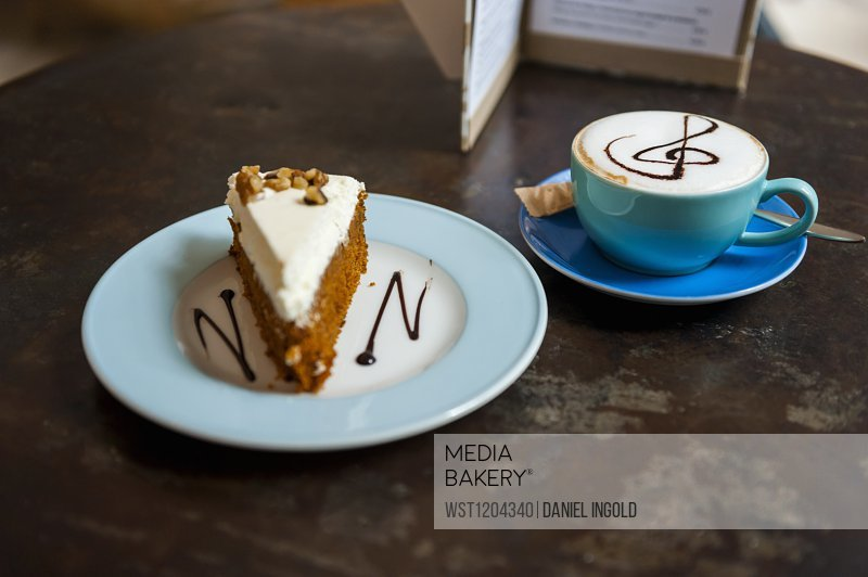 Cup of Cappuchino and piece of cake on table in a coffee shop