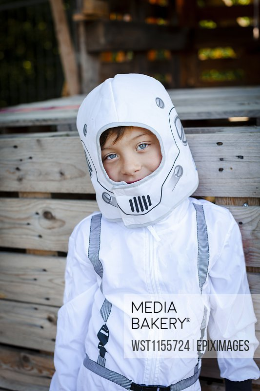 Young boy as a superhero, astronaut playing in a tree house
