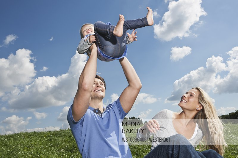 Germany, Cologne, Parents playing with girl (2-3 Years), smiling