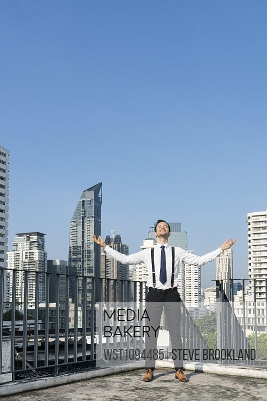 Happy and content successful business man on city rooftop
