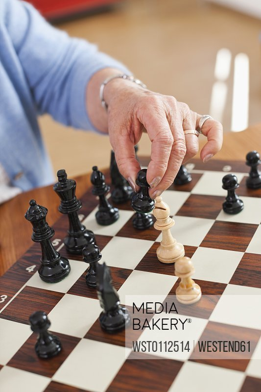 Senior woman playing chess game