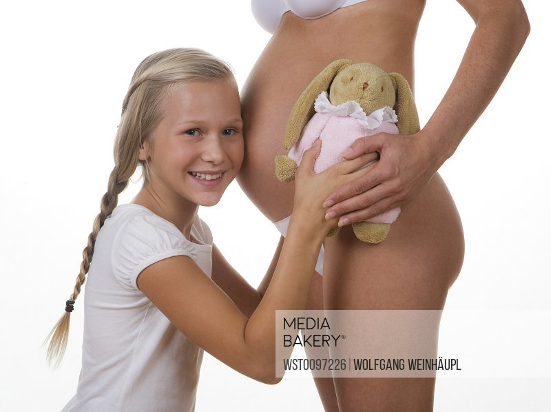 Daughter (12-13 Years) embracing her pregnant mother
