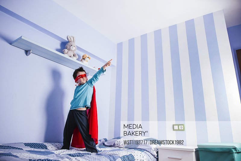 Little boy playing super hero, standing on his bed