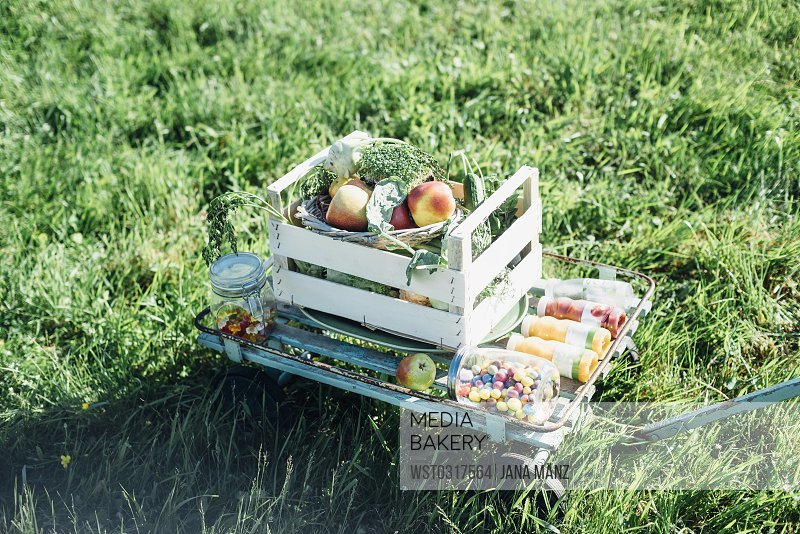 Crate with apples andsweets on cart in meadow
