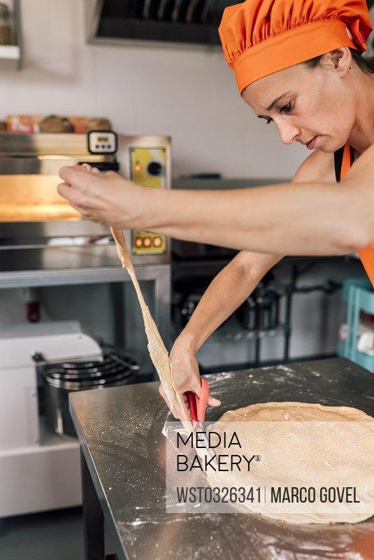 Woman preparing pizza dough