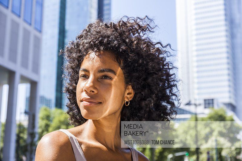 Germany, Frankfurt, portrait of content young woman with curly hair