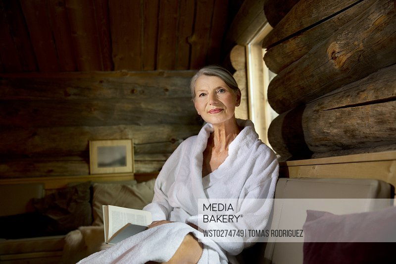 Smiling senior woman sitting on bench in bathrobe with a book