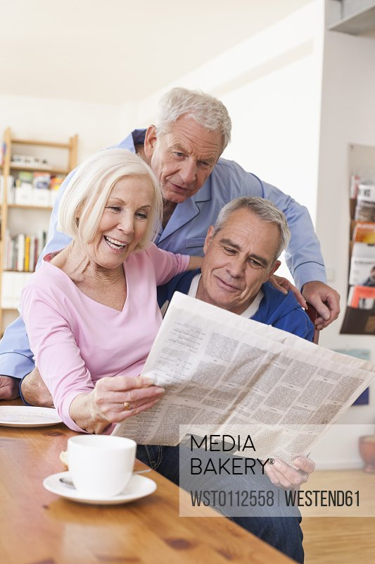 Senior men and woman reading newspaper, smiling