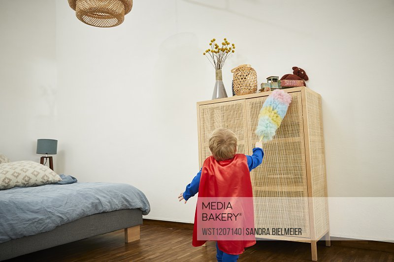 Boy wearing superman costume and cleaning with feather duster on a sideboard at home