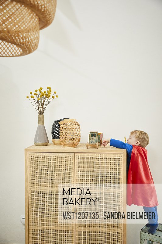 Boy wearing superman costume and reaching to wooden car on sideboard
