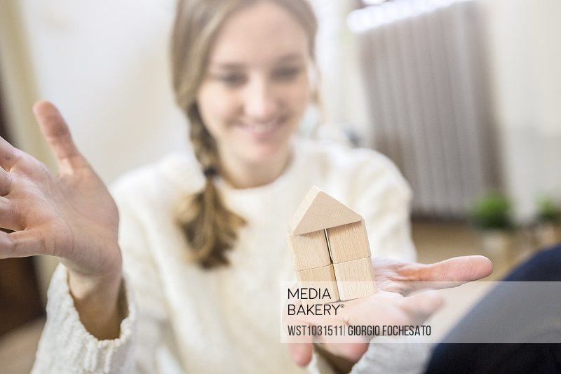 Smiling woman building house with building blocks