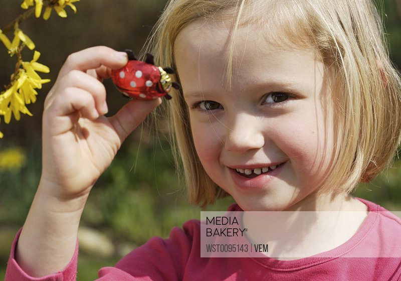Germany, Bavaria, Girl (6-7 Years) holding Easter chocolate beetle, portrait, smiling