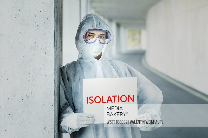 Portrait of man wearing protective clothing holding an 'isolation' sign