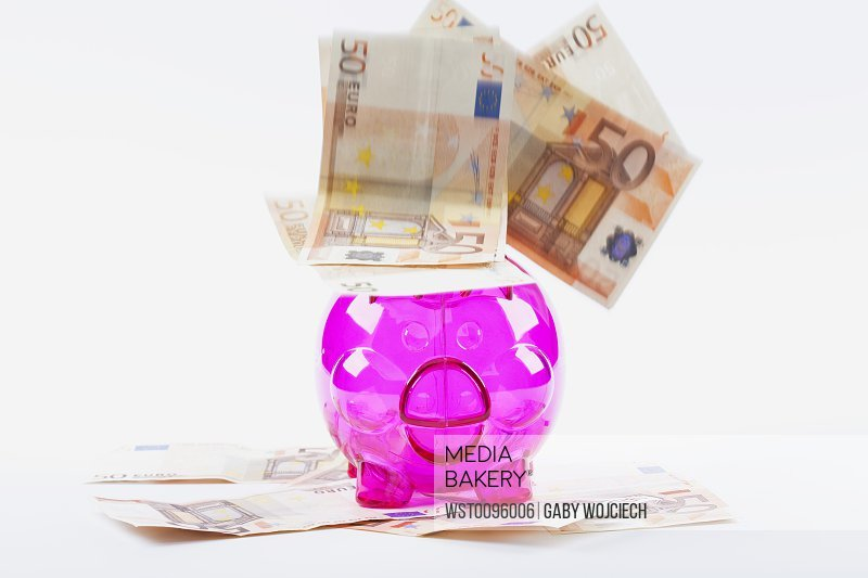 50 Euro notes falling on piggy bank