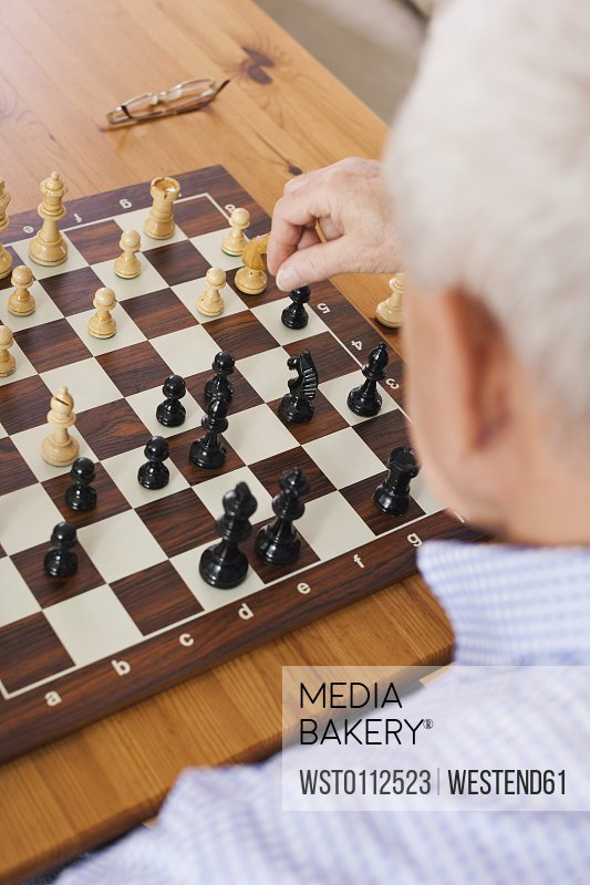 Senior man playing chess game