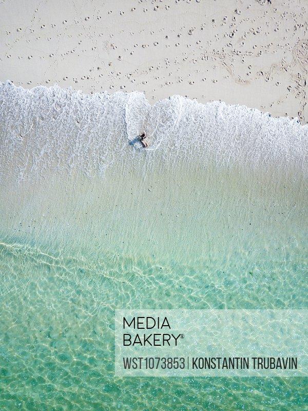 Indonesia, Bali, Young woman sitting on seashore