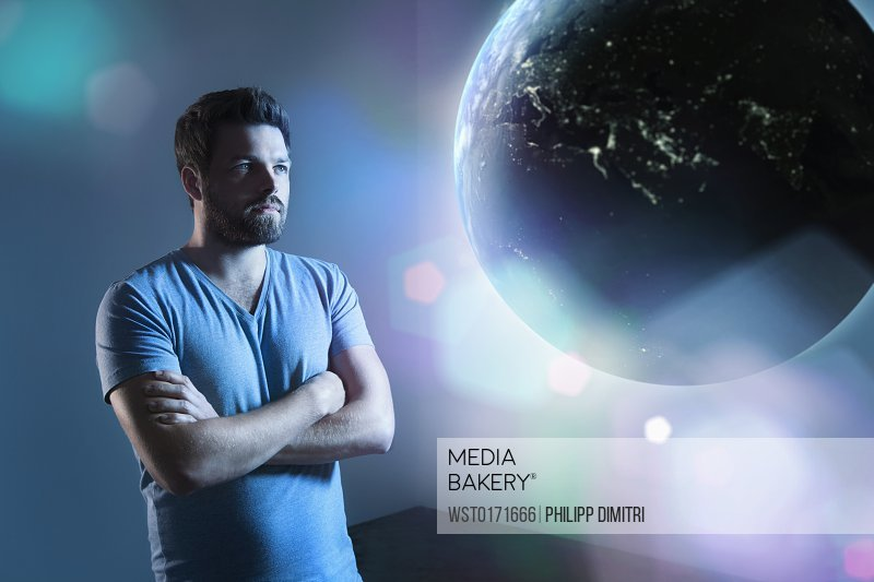 Serious looking man watching earth