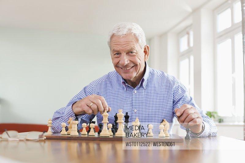 Senior man playing chess game