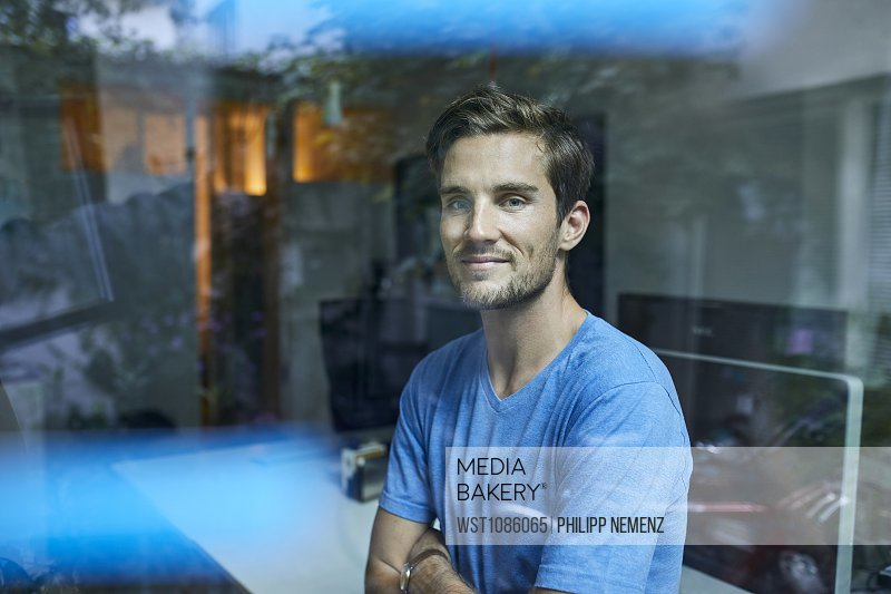 Portrait of content young man behind windowpane in an office