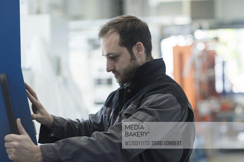 Young technician working, machine