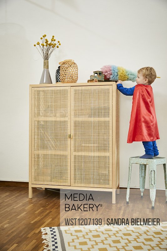 Boy wearing superman costume and cleaning toy with feather duster on a sideboard at home