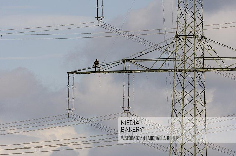 Man working on electricity pylon