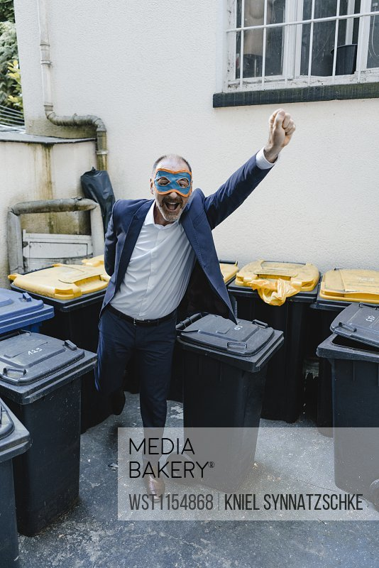 Businessman with super hero mask, fighting waste