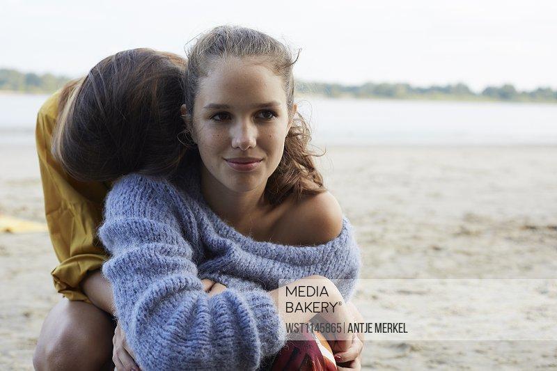 Teenage girls embarcing on beach