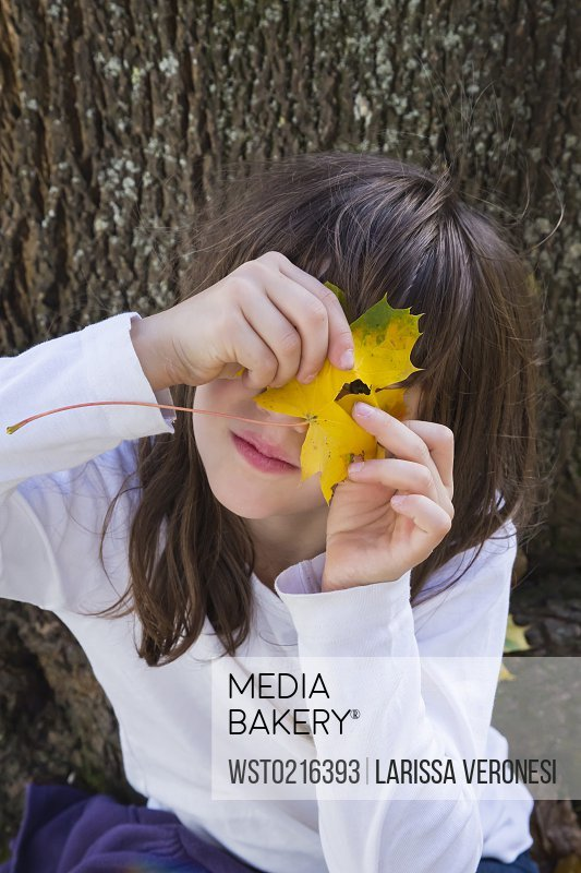 Portrait of girl peeking through hole in an autumn leaf