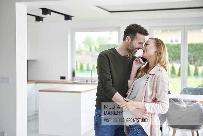 Man kissing pregnant woman in empty flat