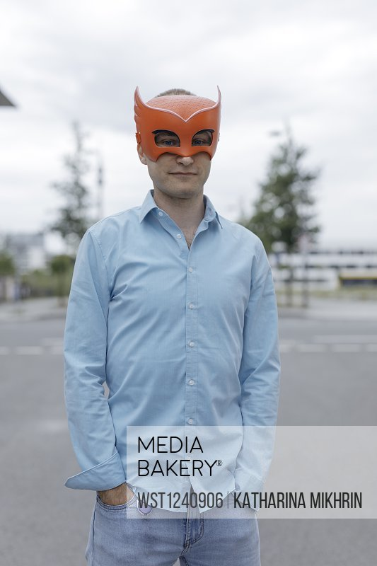 Man wearing mask with hands in pockets in city