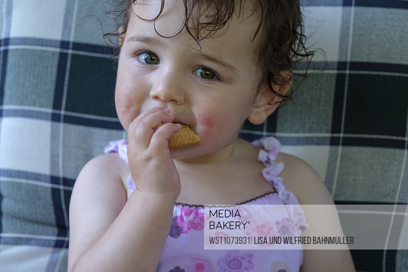 Portrait of content baby girl eating cookie