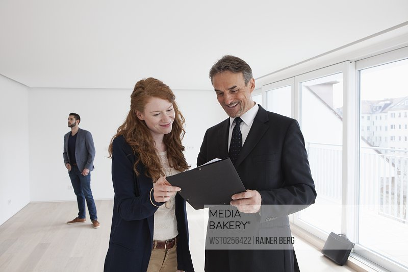 Young couple viewing flat with estate agent