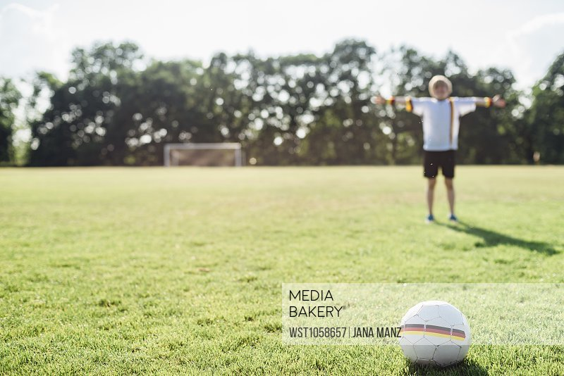 519e3aee6 Boy with outstretched arms standing on soccer field between German soccer  ball and goal