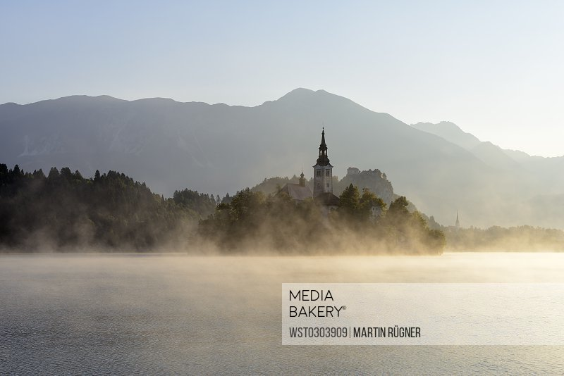 Slovenia, Gorenjska, Bled, Bled Island, Assumption of Mary's Pilgrimage Church and Lake Bled in morning fog
