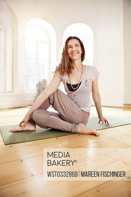 Woman in sunny yoga studio holding Eka Pada Upawistha Parivrttasana pose
