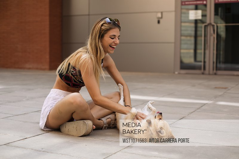 Pretty young woman smiling and caressing a dog