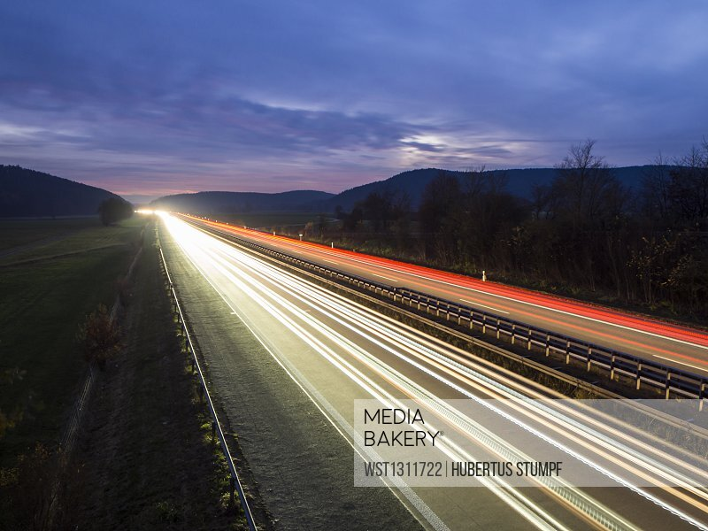 Light trails on motorway against cloudy sky