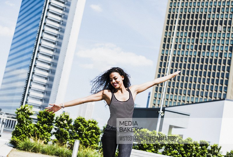 Enthusiastic young woman with outstretched arms outdoors