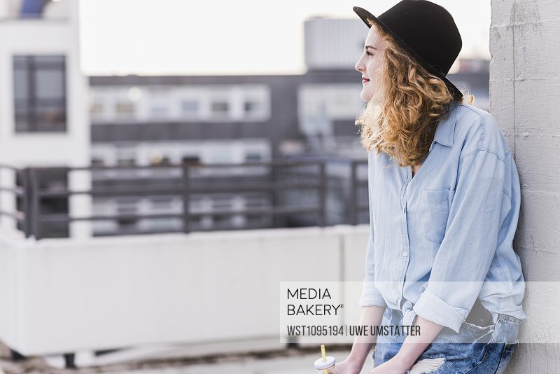 Content young woman wearing hat relaxing on roof terrace