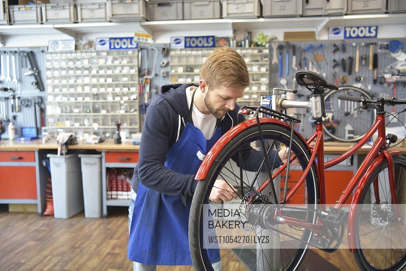 Photo by Westend 61 - Bicycle mechanic working in his repair shop