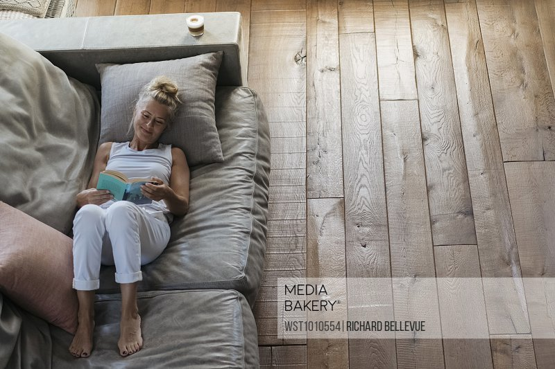 Woman Relaxing On Couch Reading Book