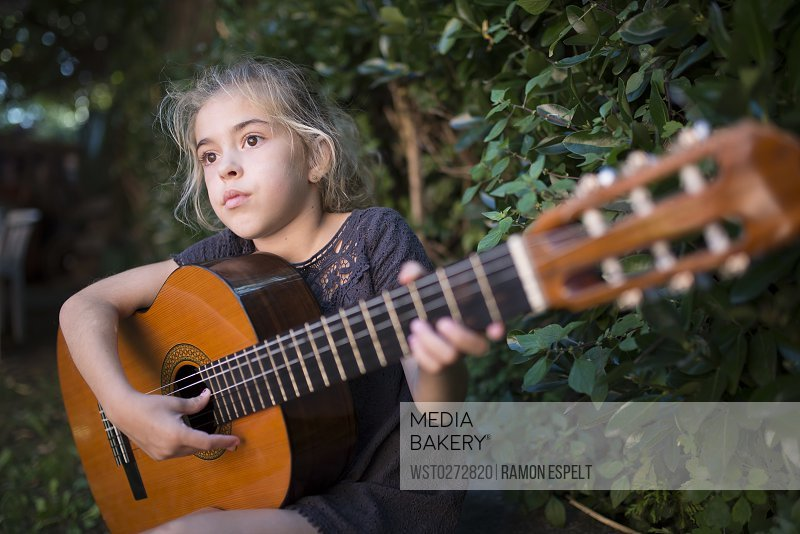 Spain, girl playing spanish guitar outdoors