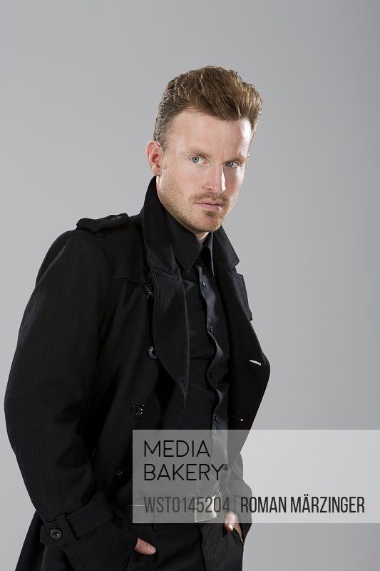 Mid adult man in black coat standing against grey background