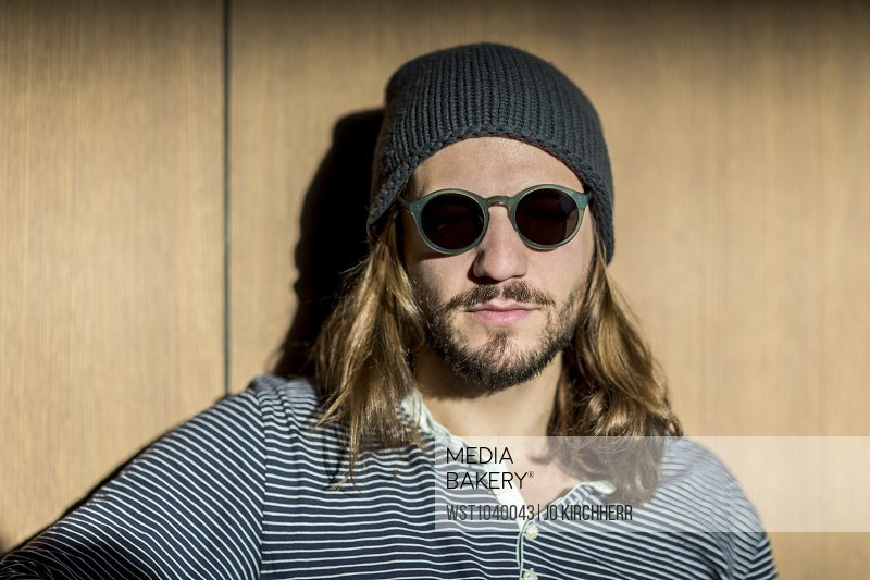 08e1c3b49b9 Portrait of bearded man with long hair wearing sunglasses and wooly hat