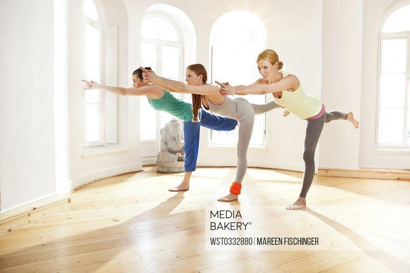 Three women in sunny yoga studio holding Virabhadrasana pose